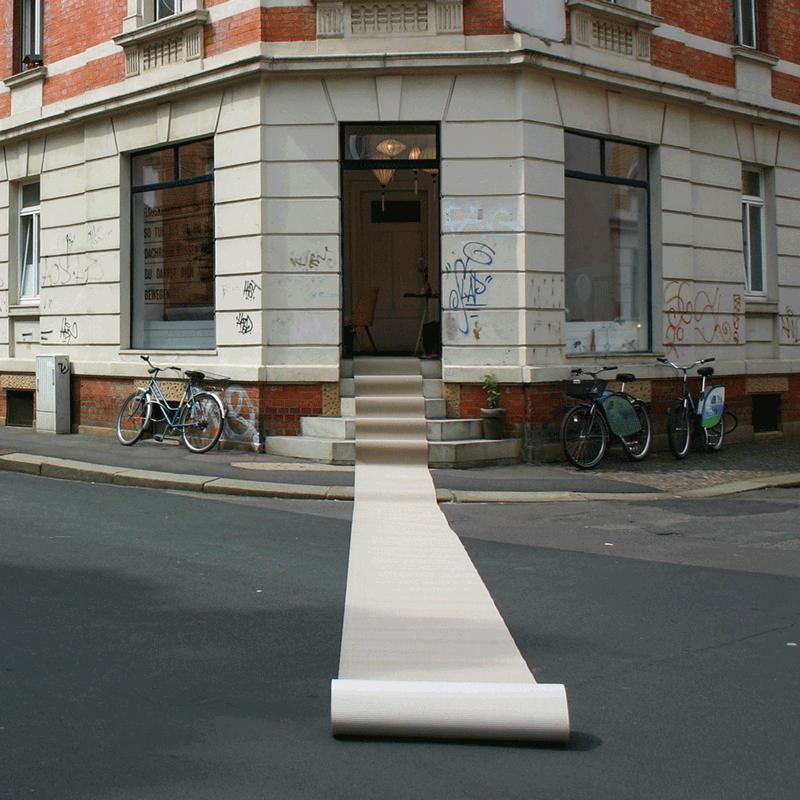 Ein Teppich rollt sich vom geöffneten Projektraum weit auf die Kreuzung aus.
