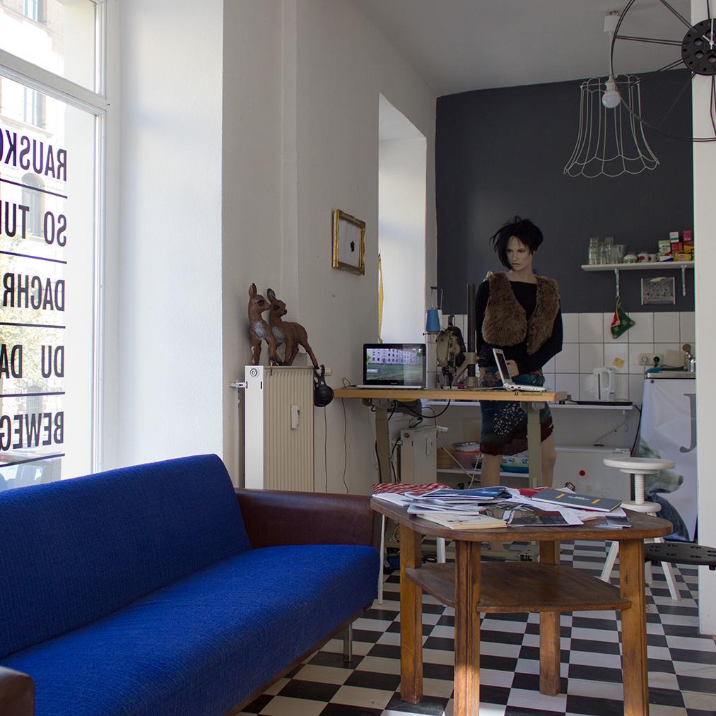Lichtdurchfluteter Raum mit schwarz-weiß-kariertem Fußboden, einem alten blauen Sofa und einer Industrie-Nähmaschine, hinter der eine Schaufensterpuppe posiert.