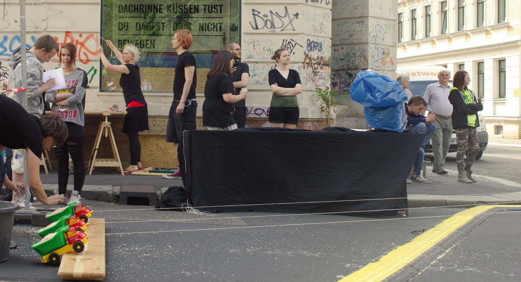 Junge Menschen bereiten ein Spielzeugauto-Wettwickeln mitten auf der Straße vor.