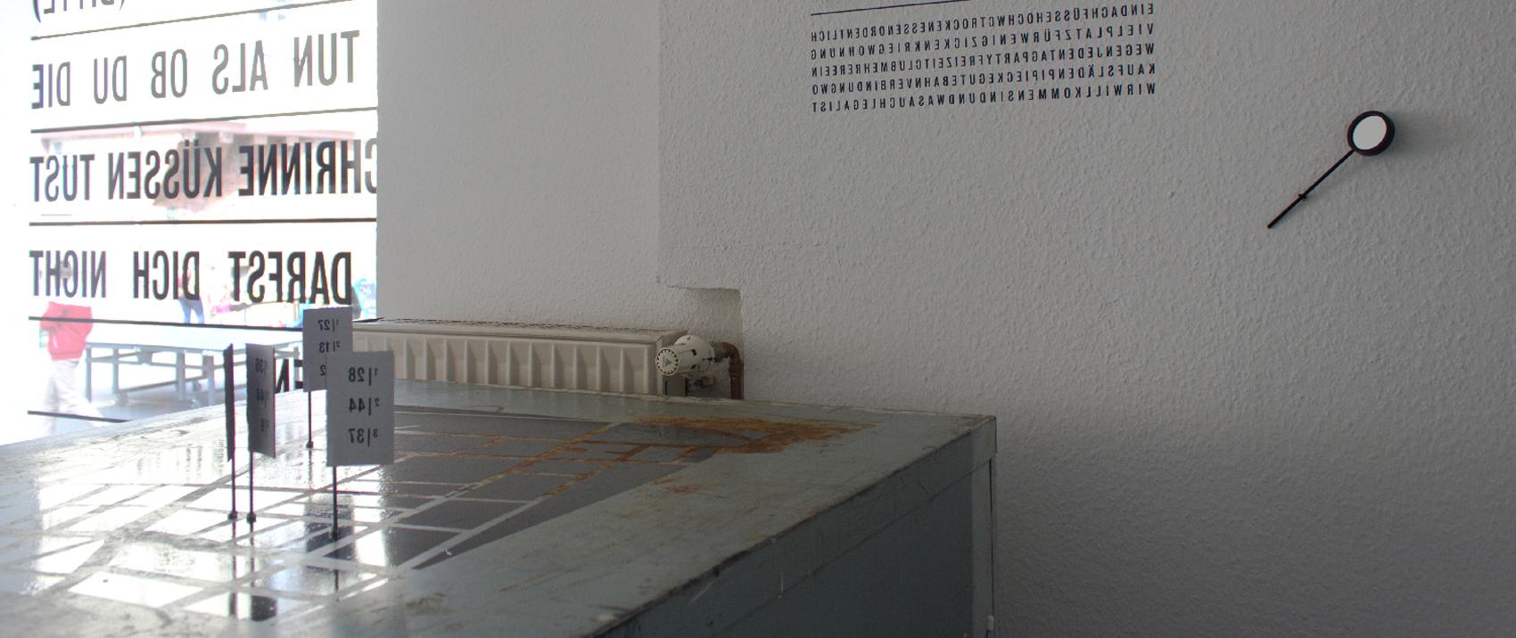 Detail der Ausstellung No Go Area mit Kartenmodell, spiegelverkehrtem Text und einem winzigem Rückspiegel an der Wand