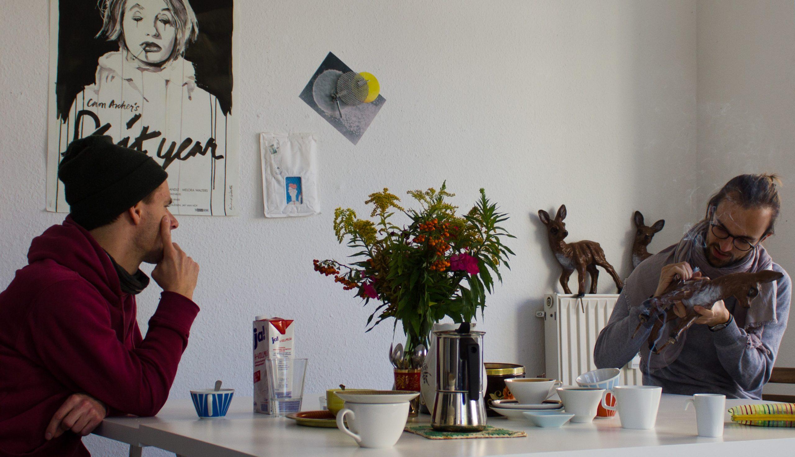 Auf einem großen Tisch stehen Blumen und unzählige Kaffeetassen. Ein junger Mann betrachtet einen anderen beim Reparieren von Plastik-Rehen.